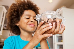 boy looking at pennies in piggy bank